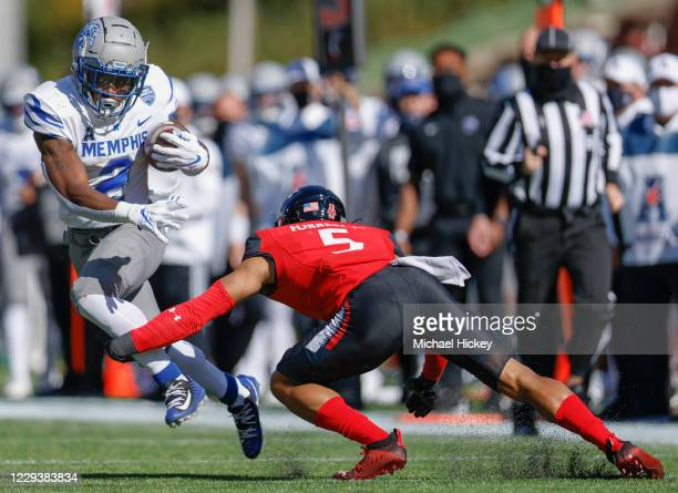 Rodrigues Clark of the Memphis Tigers evades the tackle from Darrick Forrest of the Cincinnati Bearcats during the first half at Nippert Stadium on...