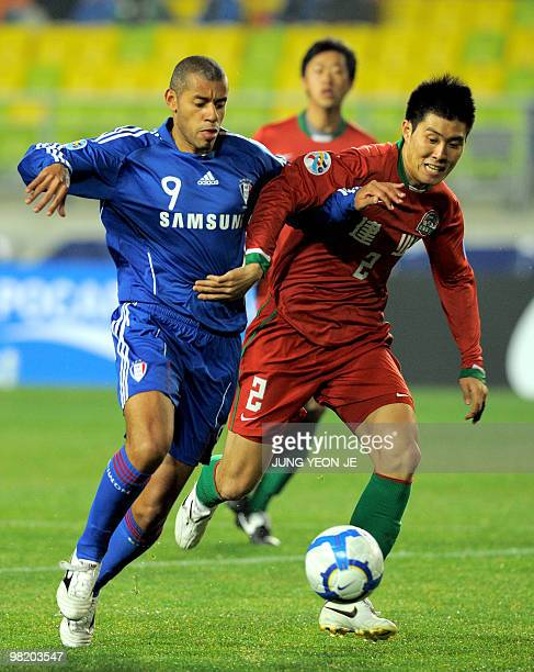Rodrigues Mota Jose Roberto of South Korea's Suwon Bluewings and Song Taelim of China's Henan Jianye fight for the ball during a Group G match of the...