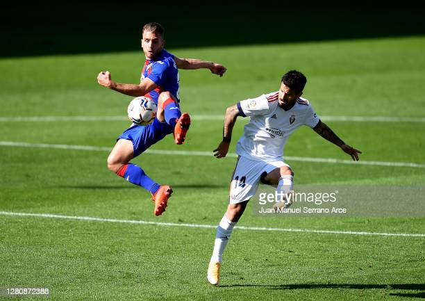 Rodrigues of Eibar beats Ruben Garcia of Osasuna to the ball during the La Liga Santander match between SD Eibar and C.A. Osasuna at Estadio...