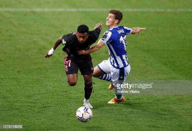 Rodrygo of Real Madrid is challenged by Aihen Munoz of Real Sociedad during the La Liga Santander match between Real Sociedad and Real Madrid at...