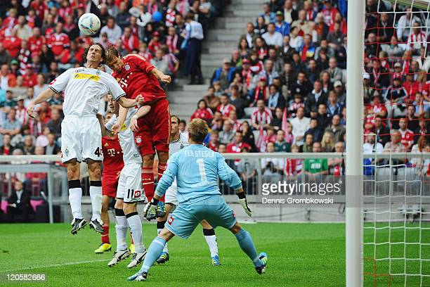 Roel Brouwers of Moenchengladbach and Holger Badstuber of Bayern jump for a header during the Bundesliga match between FC Bayern Muenchen and...