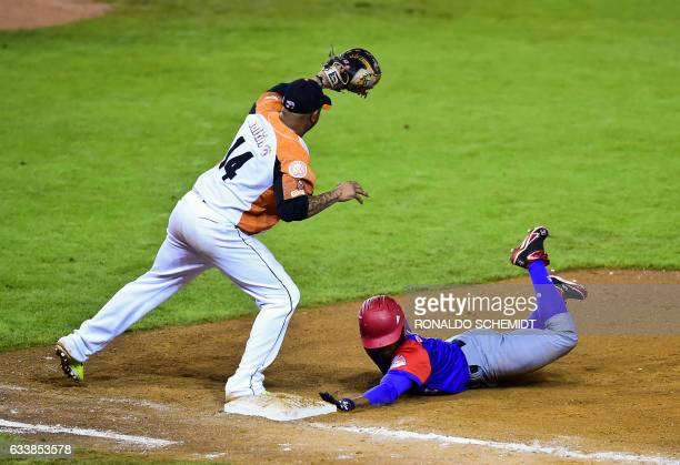 Roel Santos of Alazanes de Granma from Cuba slides safe in first base in a match against Aguilas del Zulia from Venezuela during the Caribbean...