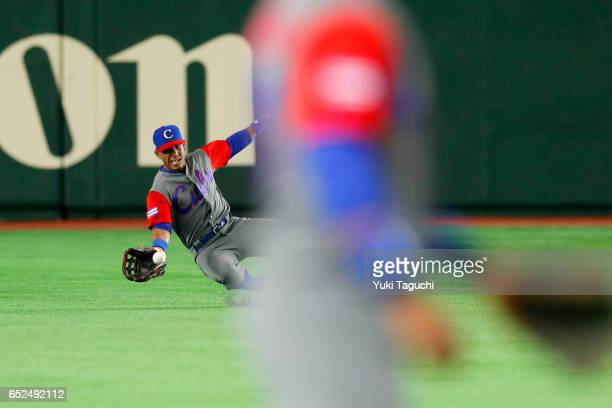 Roel Santos of Team Cuba makes sliding catch in the first inning during Game 1 of Pool E against Team Israel at the Tokyo Dome on Sunday March 12...