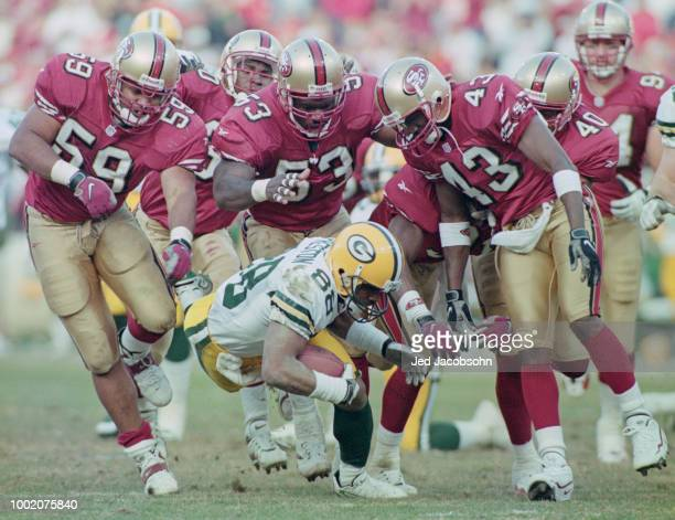Roell Preston Wide Receiver for the Green Bay Packers is tackled by the 49ers defensive line of Reggie Givens James Williams and Antonio Langham...
