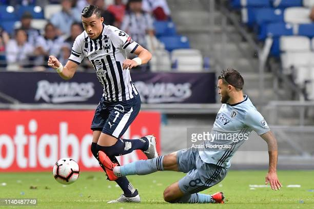 Rogelio Funes Mori of Monterrey fights for the ball with Graham Zusi of Sporting KC during the semifinal match between Monterrey and Sporting KC as...