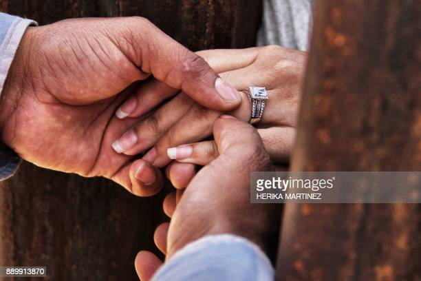 Rogelio gives Miriam her wedding ring as they get married through the border wall between Mexico and the United States during the Keep our dream...