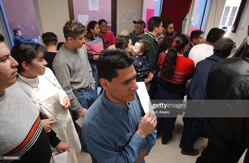 Rogelio Ibarra waits in line, holding his application, for