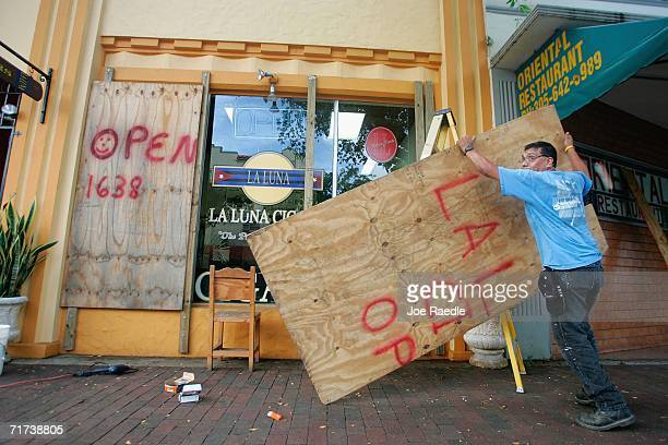 Rogelio Perez places plywood over the windows of his business as he prepares for the approaching Tropical Storm Ernesto that is threatening South...