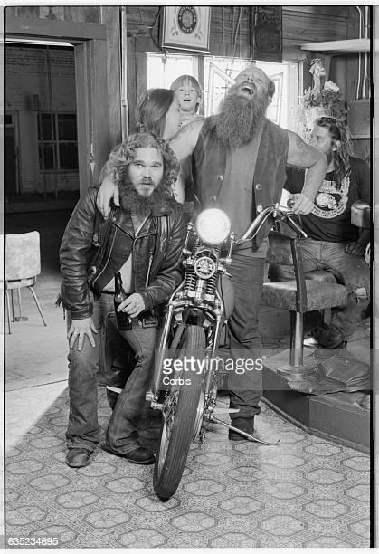 Roger and Sandy Cunningham sitting on Roger's 1946 Harley Davidson hug their friend Terry Blaine