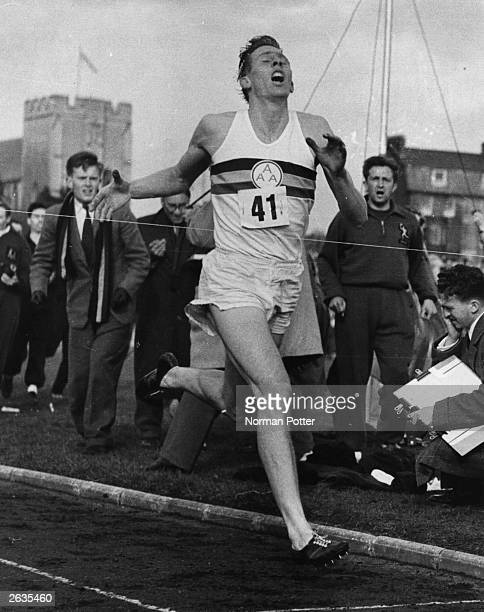 Roger Bannister crossing the tape at the end of his record breaking mile run at Iffley Road, Oxford. He was the first person to run the mile in under...