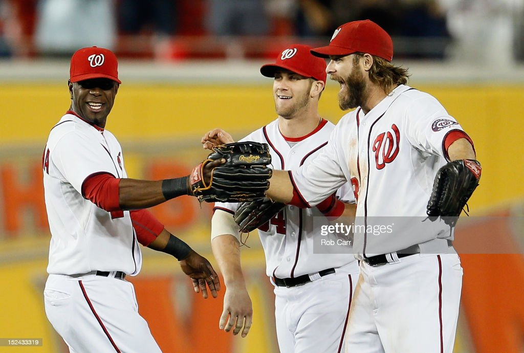 Roger Bernadina #2 (L), Bryce Harper #34 (C), and Jayson Werth #28 of the Washington Nationals celebrate after the Nationals defeated the Los Angeles Dodgers 4-1 to clinch a playoff birth at Nationals Park on September 20, 2012 in Washington, DC.