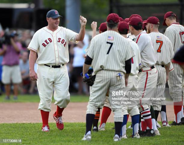 Roger Clemens is welcomed by his teammates as starting lineups are announced during the 26th annual Oldtime Baseball Game at St. Peter's Field in...