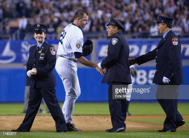 Roger Clemens of the New York Yankees shakes hands with World Trade Center disaster rescue workers one of who threw out the first pitch before a game...