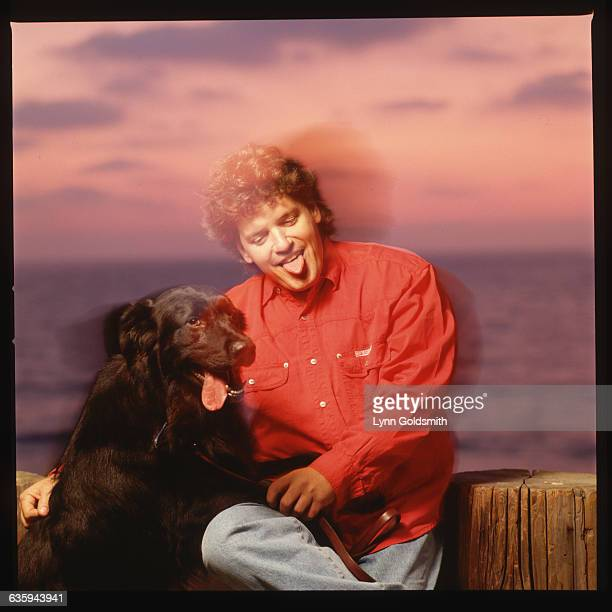 Roger Clinton singer and brother of President Bill Clinton jokingly sticks his tongue out while sitting with a black dog