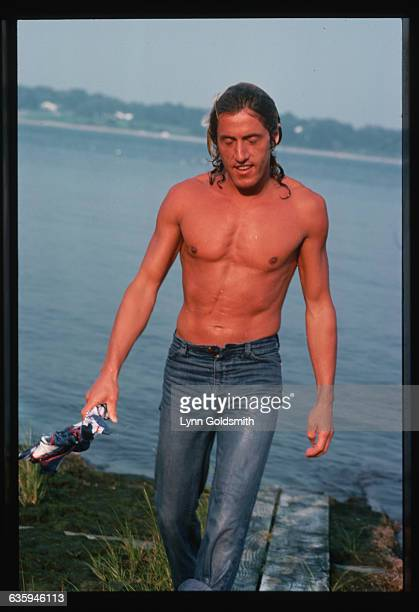 Roger Daltrey, lead singer of The Who, emerges from the water, wet T-shirt in hand.