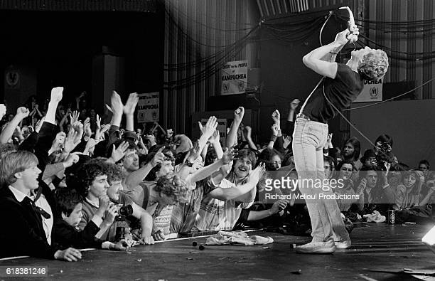 Roger Daltrey sings before a cheering crowd during a Who set at the Hammersmith Odeon in London The Who are performing along with fellow musicians...