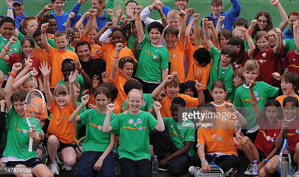 Roger Draper and Kyle Edmond and local kids at the allplay tennis park event at Clapham Common on July 4 2012 in London England Today was the launch...