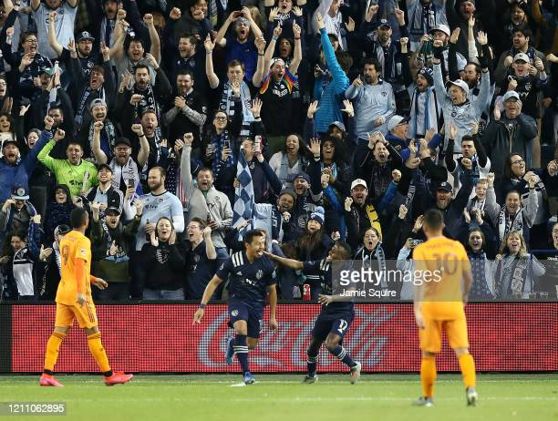 Roger Espinoza of Sporting Kansas City celebrates with Gadi Kinda after scoring during the 1st half of the game against the Houston Dynamo at...