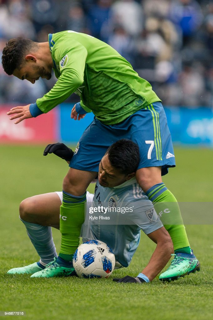Roger Espinoza #17 of Sporting Kansas City is caught under Cristian Roldan #7 of Seattle Sounders after being tripped during the second half on April 15, 2018 at Children's Mercy Park in Kansas City, Kansas.