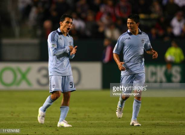 Roger Espinoza of Sporting Kansas City looks on as teammate Omar Bravo punches his hand after scoring a goal during the MLS match against Chivas USA...