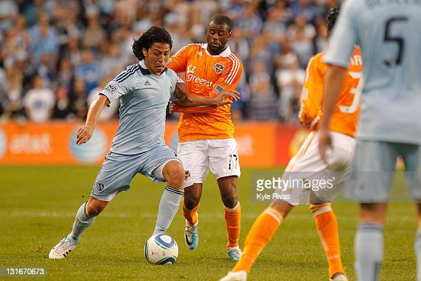 Roger Espinoza of the Sporting Kansas City attemps to fight past the defense of Luiz Camargo of the Houston Dynamo in the first half during the MLS...