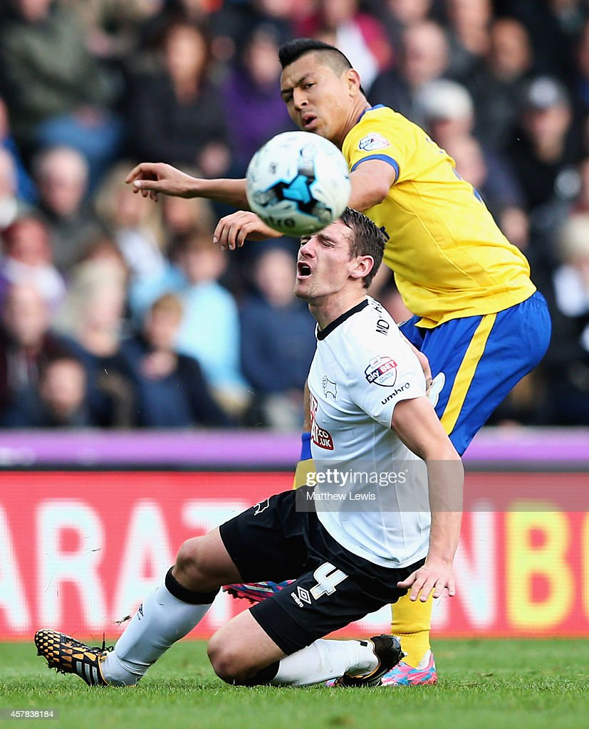 Roger Espinoza of Wigan Athletic and Craig Bryson of Derby County challenge for the ball during the Sky Bet Championship match between Derby County and Wigan Athletic at the iPro Stadium on October 25, 2014 in Derby, England.