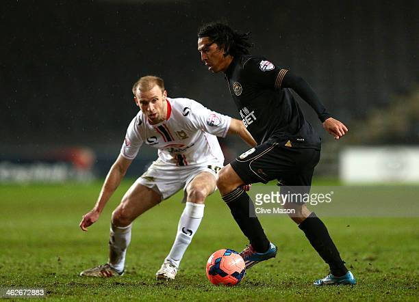 Roger Espinoza of Wigan controls the ball as Luke Chadwick of Milton Keynes closes in during the Budweiser FA Cup third round replay match between...