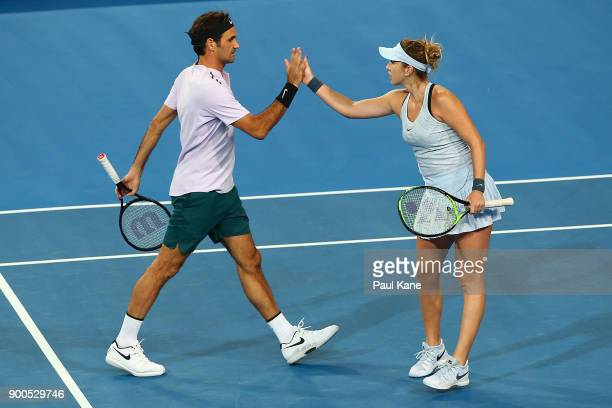 Roger Federer and Belinda Bencic of Switzerland celebrate a point in the mixed doubles match against Anastasia Pavlyuchenkova and Karen Khachanov of...