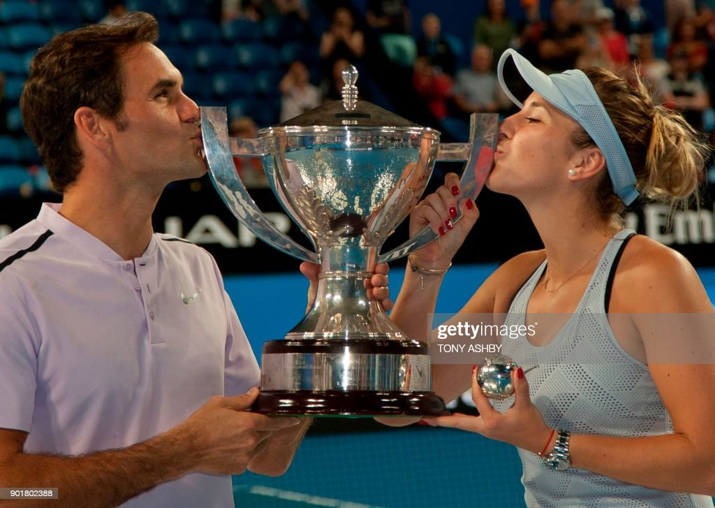 TOPSHOT - Roger Federer (L) and Belinda Bencic of Switzerland hoist the Hopman Cup after defeating Alexander Zverev and Angelique Kerber of Germany in the mixed doubles final on day eight of the Hopman Cup tennis tournament in Perth on January 6, 2018. /