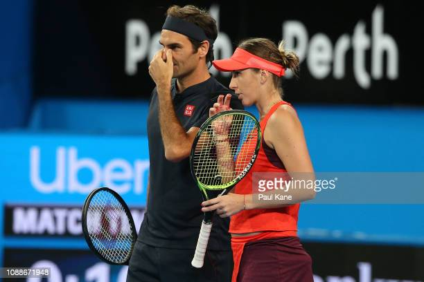Roger Federer and Belinda Bencic of Switzerland talk tactics in the mixed doubles match against Serena Williams and Frances Tiafoe of the United...