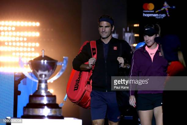 Roger Federer and Belinda Bencic of Switzerland walk out onto court past the Hopman Cup during day eight of the 2019 Hopman Cup at RAC Arena on...