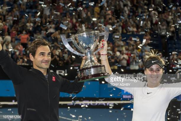 Roger Federer and his mixed doubles partner Belinda Bencic of Switzerland with the Hopman Cup after defeating runners-up Alexander Zverev and...
