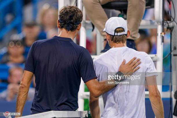 Roger Federer consoles David Goffin after Goffin retired in the second set due to an injury in their semifinal match at the Western Southern Open at...