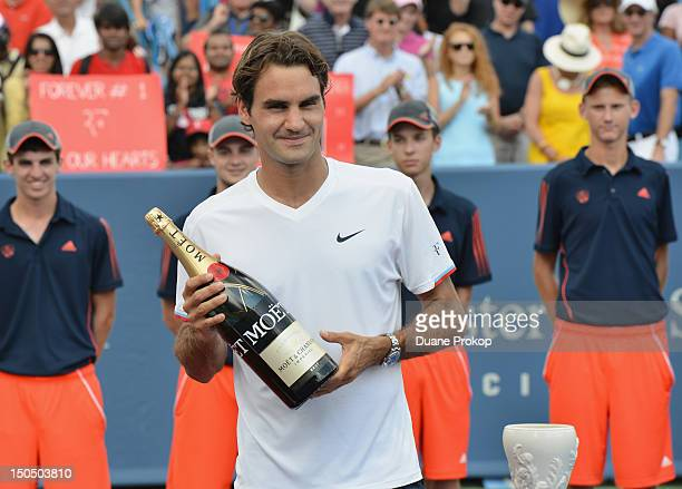 Roger Federer holds a bottle of Moet Champagne after winning his singles final match again Novak Djokovic during the debut of Moet Chandon as the...