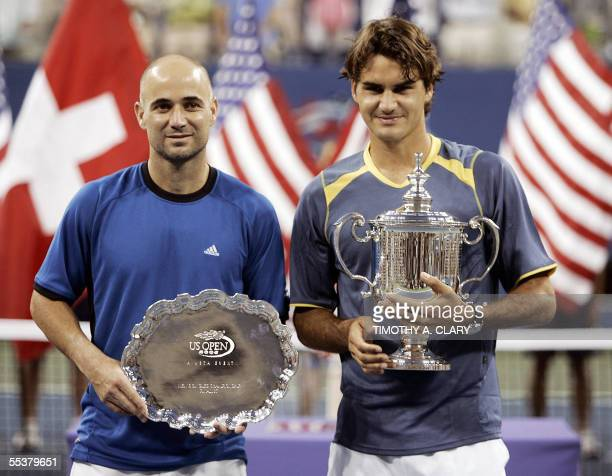 Roger Federer of Switzerland and Andre Agassi of the US pose with their trophies during the victory ceremony after the US Open final 11 September...