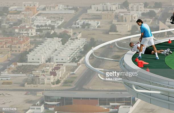 Roger Federer of Switzerland and Andre Agassi of the USA look over the edge of the 700ft high helipad after losing a ball over the side on February...