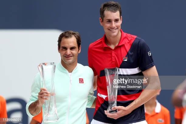 Roger Federer of Switzerland and John Isner pose for photographers at the trophy ceremony during the men's final of the Miami Open Presented by Itau...