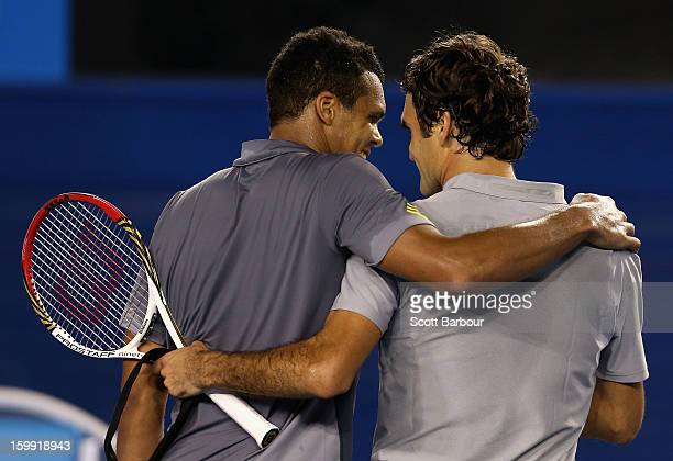 Roger Federer of Switzerland and Jo-Wilfred Tsonga of France chat after Federer won their Quarterfinal match during day ten of the 2013 Australian...