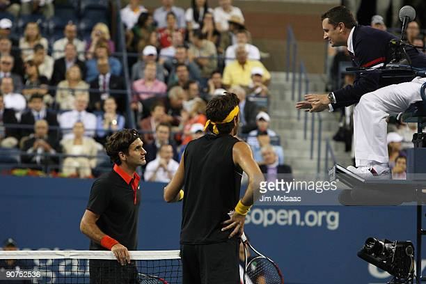 Roger Federer of Switzerland and Juan Martin Del Potro of Argentina dispute a call in the fourth set tiebreak to chair judge Jake Garner during the...
