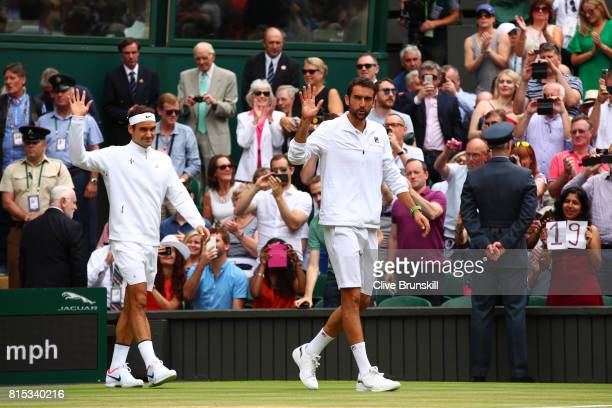 Roger Federer of Switzerland and Marin Cilic of Croatia acknowledge the crowd as they walk onto court prior to Gentlemen's Singles final on day...