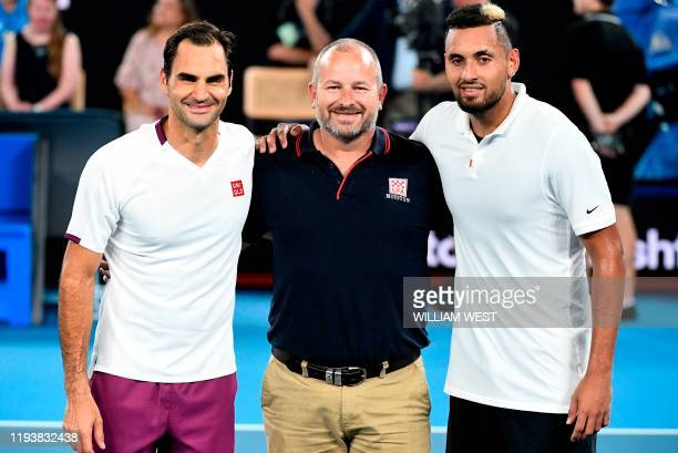 Roger Federer of Switzerland and Nick Kyrgios of Australia pose with firefighter Alistair Mason as they and other top players play in the Rally for...