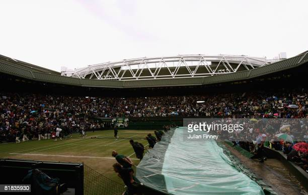 Roger Federer of Switzerland and Rafael Nadal of Spain leave the court at a rain delay during the men's singles Final match on day thirteen of the...