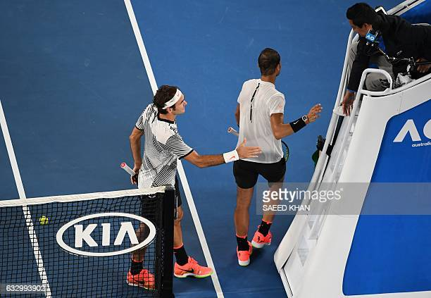 Roger Federer of Switzerland and Rafael Nadal of Spain shakes hands with the chair umpire after Federer's victory in the men's singles final on day...
