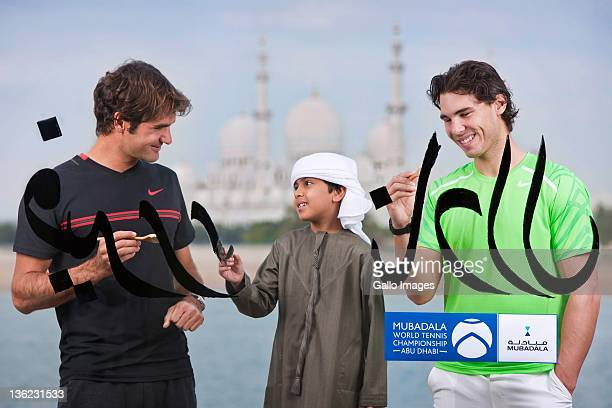 Roger Federer of Switzerland and Rafael Nadal of Spain take part in a unique Arabic calligraphy session with a young United Arab Emirates national as...