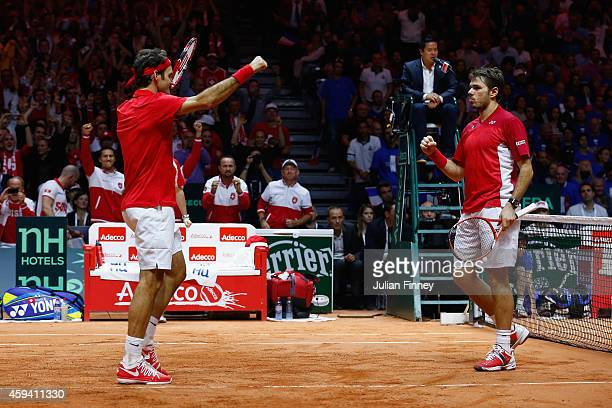 Roger Federer of Switzerland and Stanislas Wawrinka of Switzerland celebrate defeating Richard Gasquet of France and Julien Benneteau of France in...