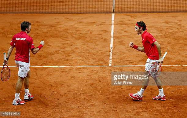 Roger Federer of Switzerland and Stanislas Wawrinka of Switzerland celebrate breaking serve in the third set against Richard Gasquet of France and...