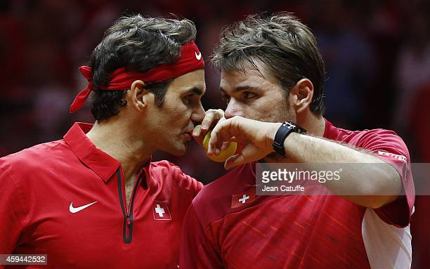 Roger Federer of Switzerland and Stanislas Wawrinka of Switzerland talk tactics against Richard Gasquet of France and Julien Benneteau of France in...