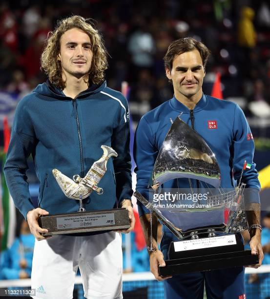 Roger Federer of Switzerland and Stefanos Tsitsipas pose with their trophy after their final match day Fourteen of the Dubai Duty Free Tennis Stadium...
