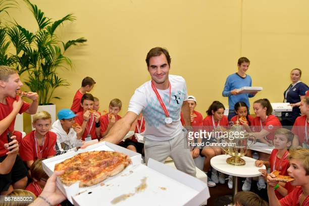 Roger Federer of Switzerland celebrates his victory with the tournament ball boys during the pizza party following the final match of the Swiss...
