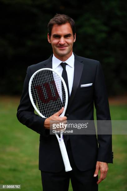 Roger Federer of Switzerland celebrates his Wimbledon record with an exclusive commemorative 8 Wilson tennis racket after his victory against Marin...